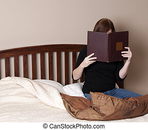 Brunette Woman Reads in Bed in a Neutral Colored Bedroom.