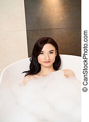 Brunette woman relaxing in bath with foam