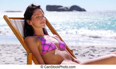 Brunette woman relaxing on a deck chair on the beach