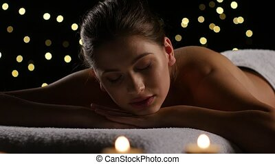 Brunette woman resting after spa treatments with burning...