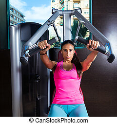 brunette woman seated chest press machine gym