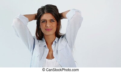 Brunette woman showing her headache against a grey background