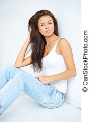 Brunette woman sitting against white wall