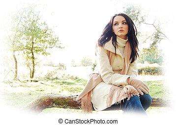 Brunette woman sitting in autumn/winter scene