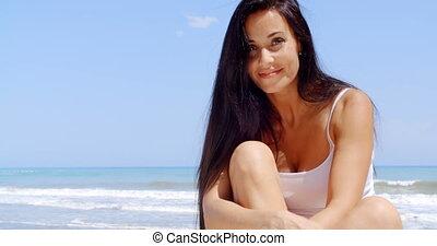 Brunette Woman Sitting in Sunshine on Beach