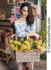 Brunette woman sitting on bike decorated with a bunch of flowers
