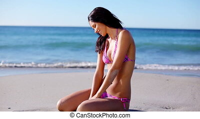 Brunette woman sitting on the sand