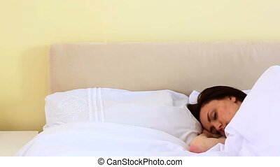 Brunette woman sleeping in her bed