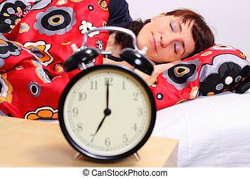 Brunette woman sleeping in her bedroom with alarm clock