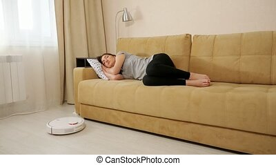 Brunette woman sleeping on the couch robot vacuum cleaner cleans the floor