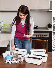 Brunette woman sowing sprouts