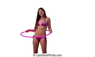 Brunette woman spinning a hula hoop against a white...