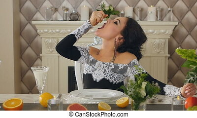brunette woman squeezes out juice of a lemon sitting at the table with fruit