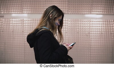 Brunette woman standing in the subway platform and using smartphone. Girl surfing the Internet while waiting the train.