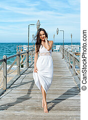 Brunette woman standing on wooden pier
