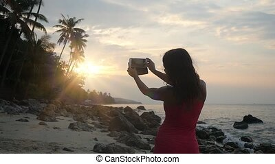 Brunette woman taking a photo of the sunset on her smartphone at the beach. slow motion. 1920x1080