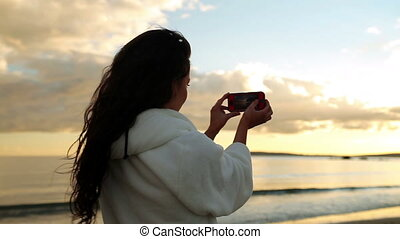 Brunette woman taking a photograph of the sunset on her...