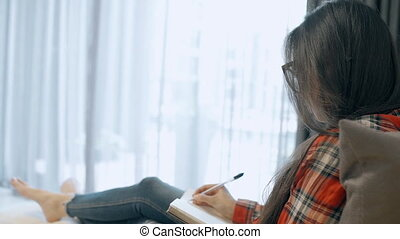 Brunette woman taking notes in diary at home.