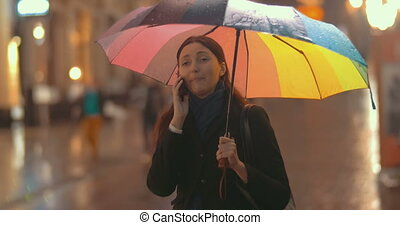 Brunette woman talks on the phone on the street on rainy day