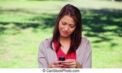 Brunette woman texting on her cellphone in a parkland