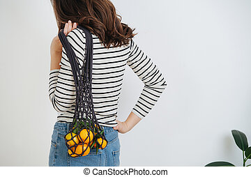 Brunette woman turned her back, posing with a net bag of mandarins over white