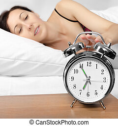 Brunette woman turning off her alarm clock
