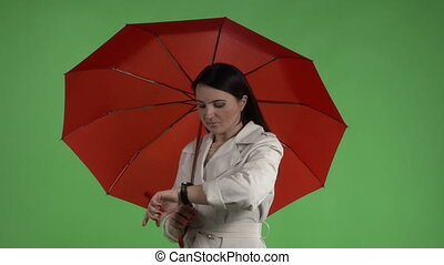 Brunette woman under red umbrella looking at watch against green screen