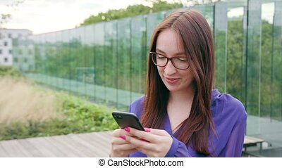 Brunette Woman Using a Phone in Town