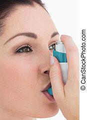 Brunette woman using asthma inhaler