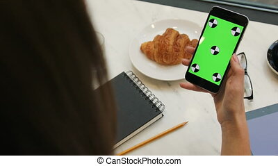 Brunette woman using smartphone with green screen in cafe. Close-up video of woman's hands holding mobile phone. Chroma key. Tracking motion. Vertical