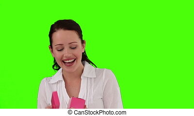 Brunette woman very pleased to open a gift