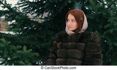 Brunette woman waist coat of brown fur in scarf walking slow motion