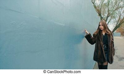 Brunette woman waist coat of brown fur walks along wall slow motion