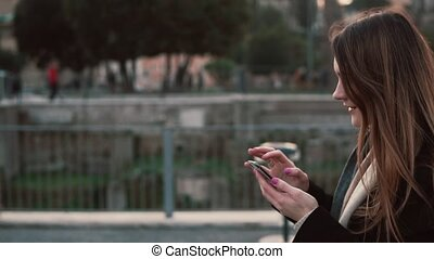 Brunette woman walking in the park and using touchscreen technology at smartphone. Girl spending time outdoors.