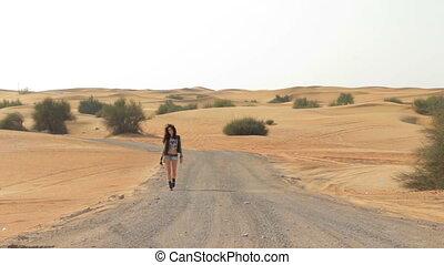 brunette woman walking on the desert road