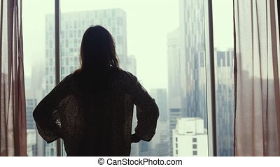 Brunette woman walks to the window stands by the big window looking out apartment on the city buildings. 3840x2160