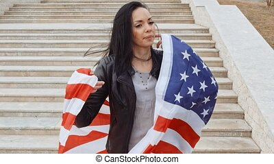 Brunette woman warapped in US flag posing in front of stairs...