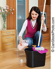 brunette woman washing floor with detergent - brunette woman...