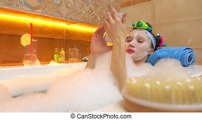 Brunette woman wearing face mask uses her mobile phone in foamy bathtub