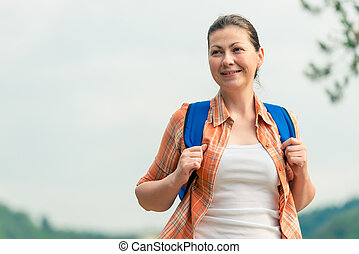 brunette woman with a backpack on the nature in a hike