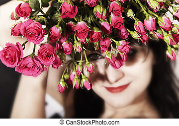 brunette woman with a bouquet of pink roses