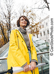 Brunette woman with bob haircut wearing glasses and yellow raincoat exploring landmarks in touristic place