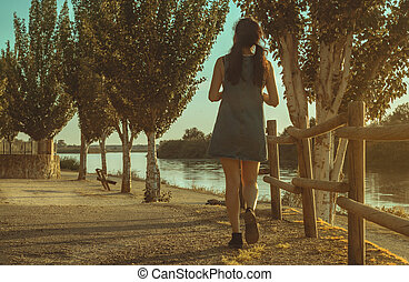 Brunette woman with cowboy dress walking beside the river at sunset