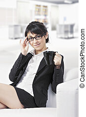 Brunette woman with cup on sofa at office