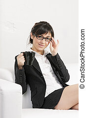 Brunette woman with cup on sofa