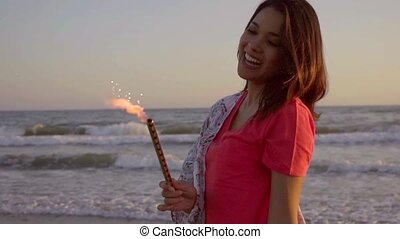 Brunette Woman With Fountain Candles On The Beach