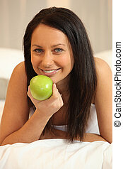 Brunette woman with green apple