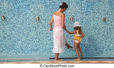 Brunette woman with her daughter wash their feet under water stream in spa center