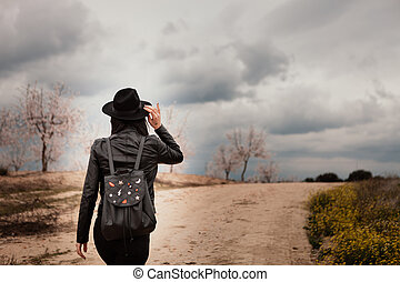 Brunette woman with leather jacket walking on a path