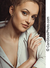 Brunette woman with natural makeup in striped shirt